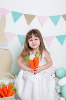 Pasen! mooi meisje in witte kledingszitting met paashazen en wortelen. konijn en kleurrijke eieren. vele verschillende kleurrijke eieren, kleurrijk pasen-binnenland. landbouw. kind en tuin.