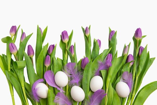 Pasen. mooie lichtpaarse tulpen met geïsoleerde paaseieren en veren. lentebloemen en planten.