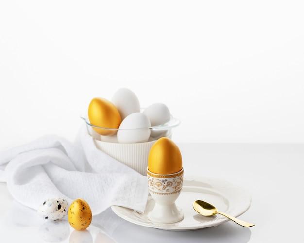 Pasen ontbijt concept. zacht gekookt ei op een witte plaat met gouden en witte paaseieren