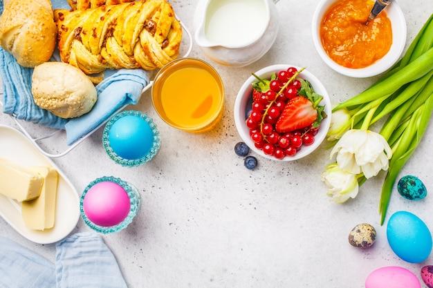 Pasen ontbijttafel. gekleurde eieren, bloemen, melk, sap en jam, witte achtergrond. bovenaanzicht, pasen-concept, kopie ruimte.