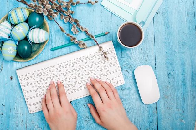 Pasen op de kantoorwerkplek op blauwe houten tafel. vrouwelijke hand op een computertoetsenbord en een kopje koffie