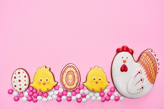 Pasen-peperkoekkippen en eieren over roze achtergrond