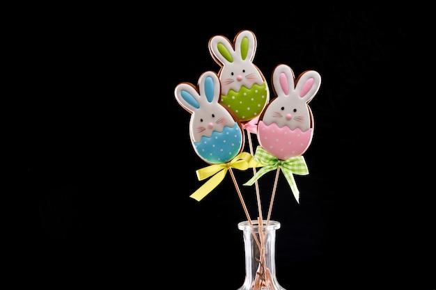 Pasen-peperkoekkonijntjes met kleurrijk suikerglazuur op stok