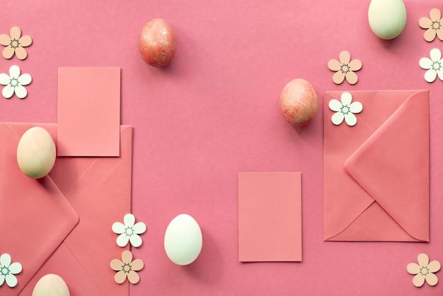 Pasen plat lag in koraal kleur met beschilderde eieren, kaarten, enveloppen en decoratieve bloemen