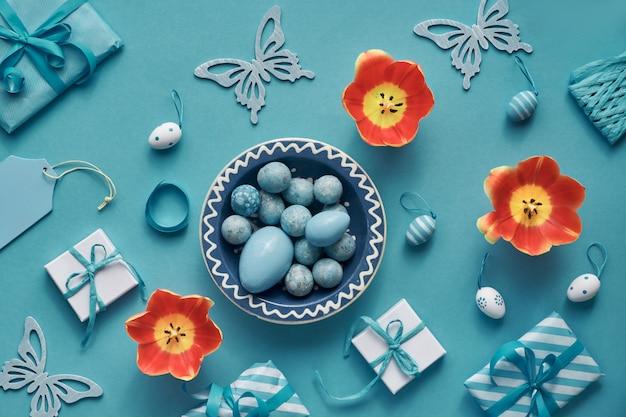 Pasen plat lag in mint, wit en oranje met tulpen, eieren, geschenkdozen en lente decoraties
