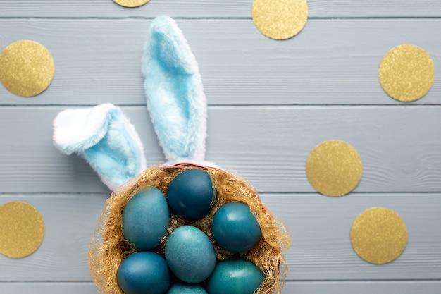 Pasen plat lag met blauwe eieren in de mand en grappige konijnenoren