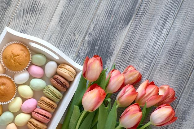 Pasen plat lag met oranje tulpen en snoepjes jn een decoratief dienblad op geweven grijs hout