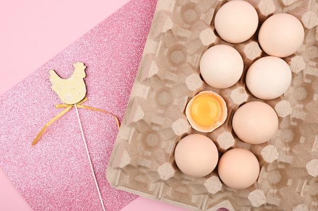 Pasen roze. ei op een houten lepel. een lade van eieren op een witte en roze achtergrond. eco dienblad met testikels. minimalistische trend, bovenaanzicht. eiertray. pasen concept.