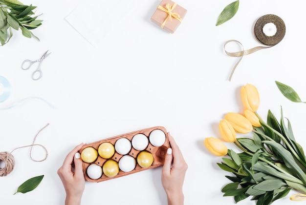 Pasen-samenstelling: de vrouwelijke handen zetten op de tafel een dienblad met gekleurde eieren