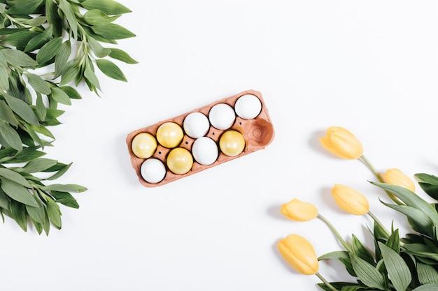 Pasen-samenstelling: een dienblad met gekleurde eieren en tulpen