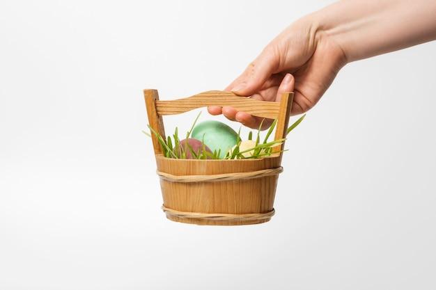 Pasen-samenstelling, eieren in een trog met groen gras in de hand van een vrouw. goed voor een banner voor de site, isoleer.