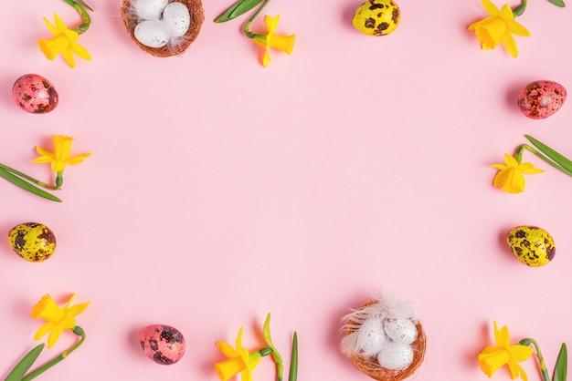 Pasen samenstelling. frame gemaakt van paaseieren en narcissen lentebloemen op pastel roze achtergrond. plat lag