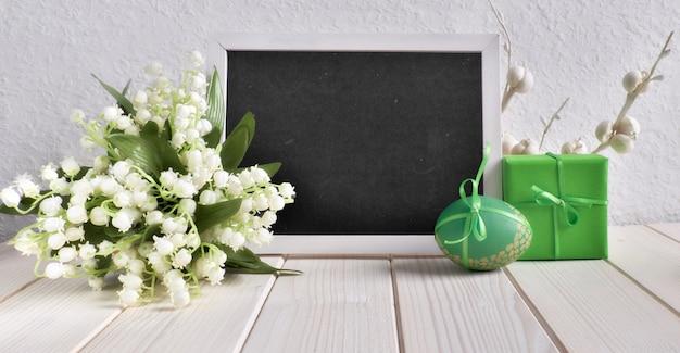 Pasen-samenstelling met bord met ceramische kip, eieren en en lelietje-van-dalenbloemen wordt verfraaid, tekst die