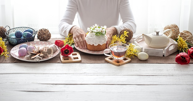 Pasen-samenstelling met cake in vrouwelijke handen, thee, bloemen, eieren en decordetails. concept van de vakantie met het gezin van pasen.