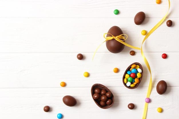 Pasen-samenstelling met chocolade-eieren en chocoladekonijn op houten achtergrond