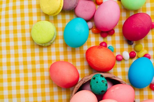 Pasen-samenstelling met gekleurde eieren en helder suikergoed op geel tafelkleed