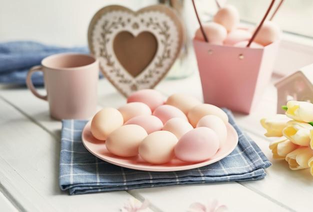 Pasen-samenstelling met gele tulpen en roze eieren