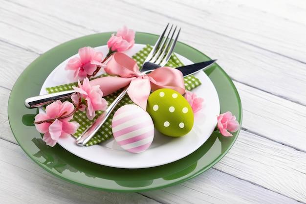 Pasen-samenstelling met kleurrijke eieren en bloemen op plaat op houten lijstachtergrond