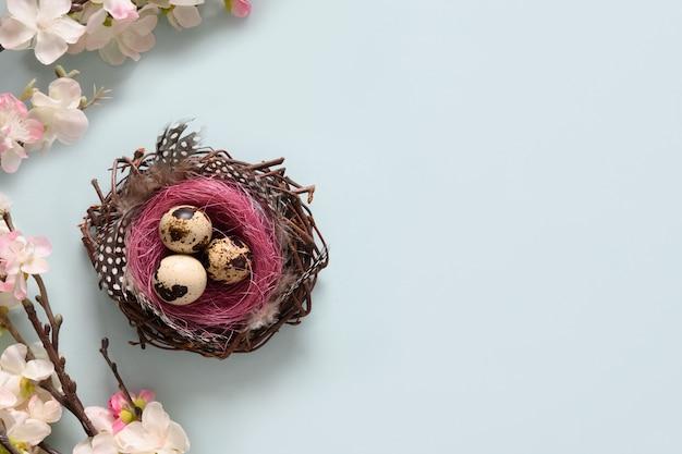 Pasen-samenstelling met kwarteleitjes in nest en lentebloemen op blauw.