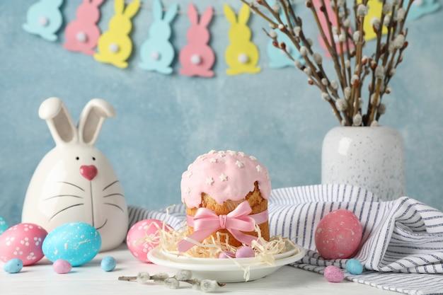 Pasen-samenstelling met pasen-cake en eieren op witte houten lijst tegen blauwe oppervlakte