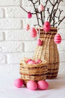 Pasen-samenstelling met versierde boomtakken in een rieten vaas en roze gekleurde eieren in rieten mand op witte achtergrond. kopieer ruimte