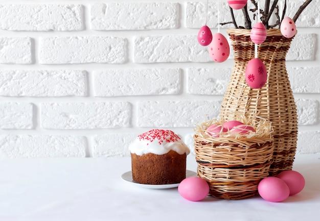 Pasen-samenstelling met versierde boomtakken in een rieten vaas, roze gekleurde eieren en cake op witte achtergrond. kopieer ruimte