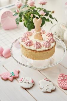 Pasen-samenstelling met zoete cake met aardbeisuikerglazuur, roze eieren en rozen
