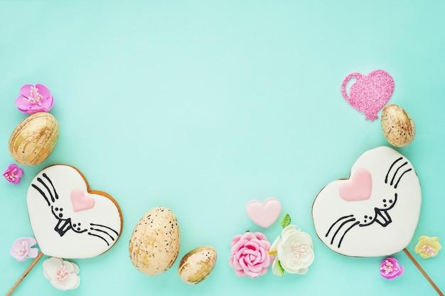 Pasen-samenstelling op een blauwe achtergrond. peperkoekkoekjes met een beschilderd konijnengezicht, gouden eieren, papieren bloemen en harten. platte lay-out, bovenaanzicht, ruimte voor kopiëren.