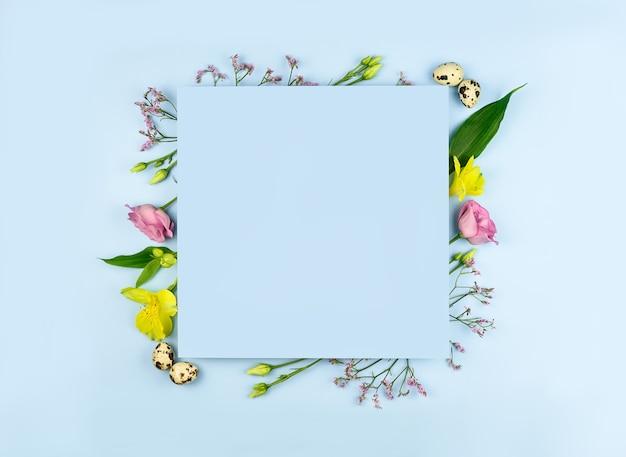Pasen samenstelling. paaseieren, bloemen, papier blanco op pastel blauwe achtergrond. plat leggen, bovenaanzicht, kopie ruimte, mock up.