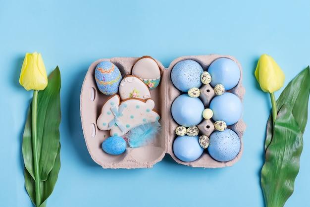 Pasen-samenstelling van ambachtelijke geschilderde eieren in document vakje, tulpenbloemen en gebakken koekjes op blauw.