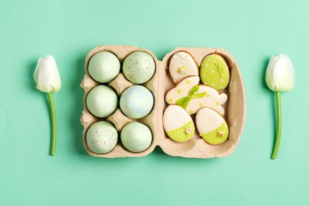 Pasen-samenstelling van ambachtelijke geschilderde eieren in document vakje, tulpenbloemen en gebakken koekjes op groen.