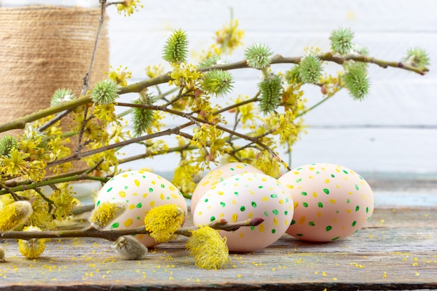 Pasen-samenstelling van bloeiende wilgentakjes, kornoeljes en paaseieren met een patroon van gele en groene stippen op een houten retro ruimteclose-up als achtergrond