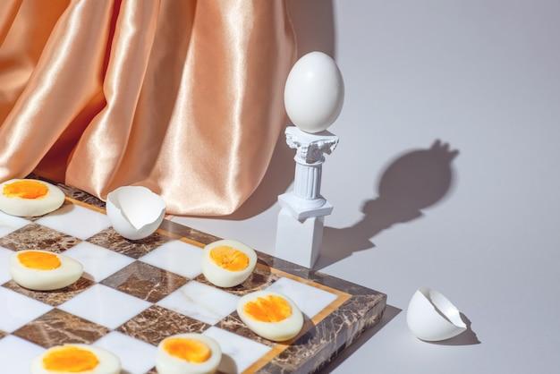 Pasen-schaakspel met verse en gekookte eieren, stillevenconcept