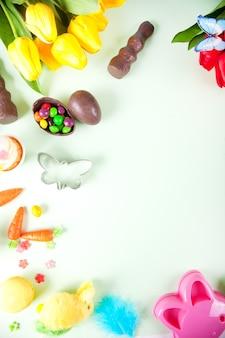 Pasen set met kleurrijke eieren, wortelen, snoep, cupcake. bovenaanzicht. kopieer ruimte.