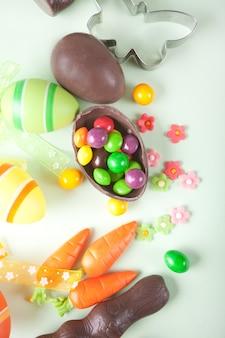 Pasen set met kleurrijke eieren, wortelen, snoep, cupcake. bovenaanzicht.