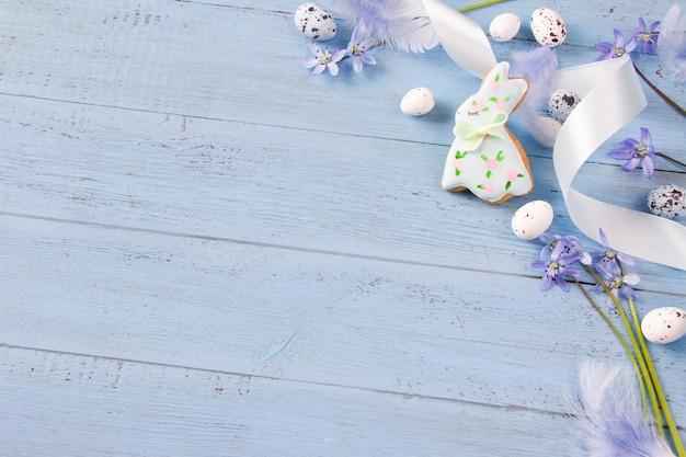 Pasen-sjabloon - paashaaskoekjes, sneeuwklokje bloemen, paaseieren en veren op blauwe houten plank.