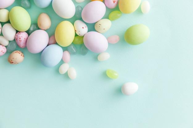 Pasen snoep chocolade-eieren en jellybean geïsoleerd op blauwe achtergrond