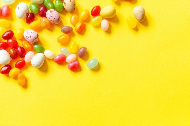 Pasen snoep chocolade-eieren en jellybean snoepjes geïsoleerd op trendy gele achtergrond