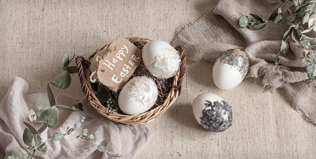 Pasen-stilleven met eieren in een rieten mand. vrolijk pasen-concept.