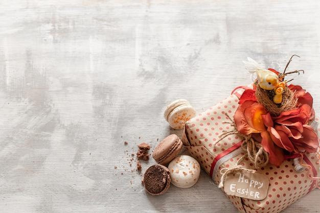 Pasen-stilleven met gift en snoepjes op houten.