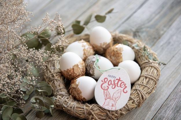 Pasen-stilleven met versierde paaseieren en decoratief nest op een houten oppervlak met droge twijgen. gelukkig pasen wenst concept.