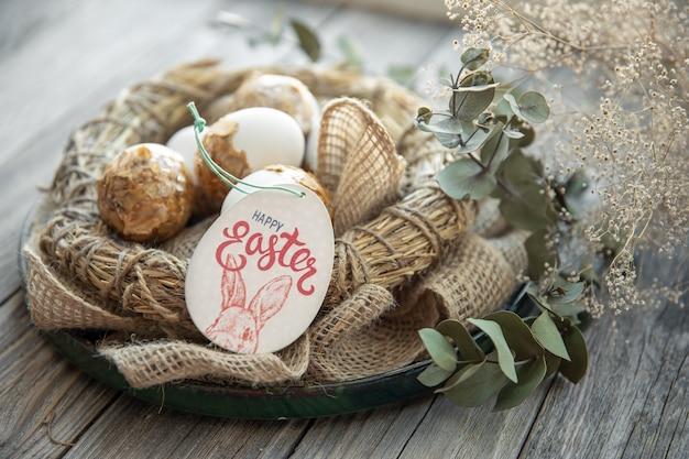 Pasen-stilleven met versierde paaseieren en decoratief nest op een houten oppervlak