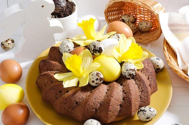 Pasen-stilleven, pasen-cake met geverfte eieren in een nest, gele narcissen op een witte rustieke houten achtergrond