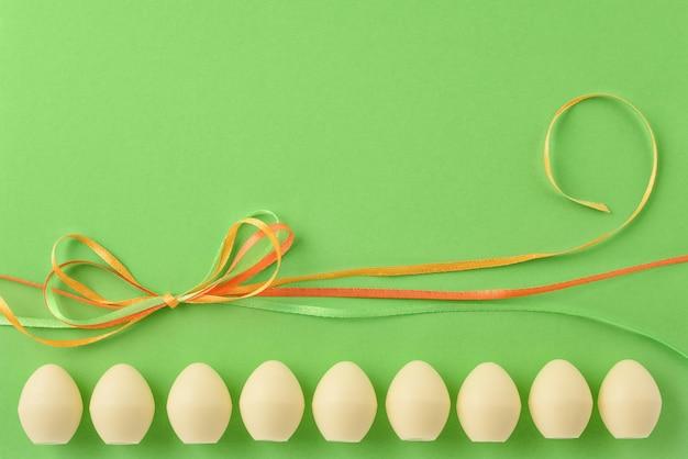 Pasen stilleven. witte chocolade-eieren en gekleurde linten op de groene achtergrond. kopieer ruimte.