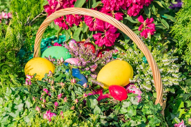 Pasen straatdecoratie. rieten mand vol beschilderde paaseieren, cake en bloemen.