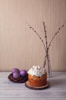 Pasen-taarten versierd met marshmallows en beschilderde paaseieren in een rieten nest met wilg op een lichte achtergrond.