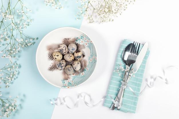 Pasen tafel instelling concept met plaat versierd lentebloemen met kwarteleitjes, zachte witte bloemen, bestek op servet op witte en lichtblauwe achtergrond.