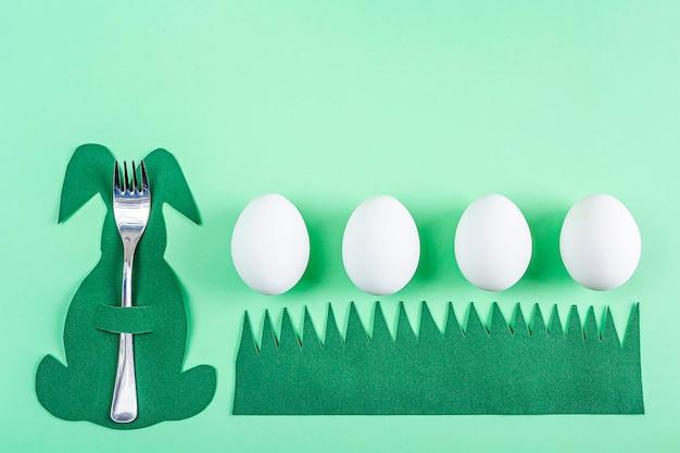 Pasen tafel instelling. leuke grappige creatieve bestekhouder in de vorm van groen konijntje en witte eieren op groene achtergrond. diy en de creativiteit van kinderen. pasen-achtergrond met exemplaarruimte voor tekst.