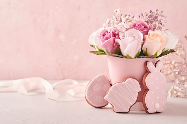 Pasen tafeldecoratie met mooie boeket roze rozen bloemen in vaas