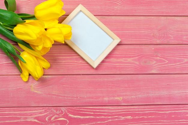 Pasen, vakantie, traditie en object - close-up van gekleurde eieren en tulpenbloemen over houten planken